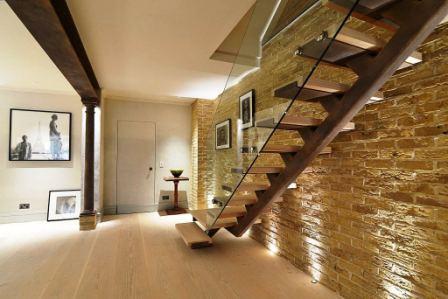 Ocelové páteřové schodiště s dřevěnými stupnicemi a skleněným zábradlím