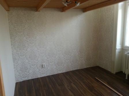 Místnost doplněná o stěnu s tapetou jemného vzoru