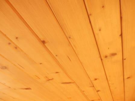 Dřevěný obklad v interiéru působí na psychiku člověka velmi příznivě. I z tohoto důvodu jsou dřevěné obklady, zejména v podkroví, oblíbené. Zhotovení dřevěného obkladu je rychlé, jednoduché a cenově dostupné.  Proč je dřevěný obklad v interiéru vhodný? Palubky jsou nejčastěji vyrobeny ze smrkového či modřínového dřeva. Dřevěné obklady vytváří v místnosti zdravé mikroklima tím, že jsou schopny regulovat vlhkost vzduchu v prostředí. Když je vlhkost nadměrná, dřevo vlhkost absorbuje a jakmile vlhkost v místnosti poklesne, vlhkost opět uvolní do okolí. Mimo to je dřevo dobrý akustický a tepelný izolant, na dotek je teplé a příjemné. Dřevo interiér zútulní a v některých případech také opticky zmenší, čí zvětší. Záleží na použitém druhu dřeva. Tmavé cizokrajné dřevo interiér opticky zmenší, zatímco světlé odstíny dřeva interiér rozjasní.  Povrchová úprava dřeva Před samotnou montáží obkladu na stěnu a strop je vhodné dřevo opatřit ochranným nátěrem, který nejen krásně zvýrazní přirozenou texturu dřeva, ale především jej bude chránit před UV zářením a biologickými škůdci. Dřevěné palubky se ošetřují z lícové strany a z bočních stran.  Pro ošetření dřeva se používají nejčastěji ochranné lazury na dřevo určené do interiéru, laky a vosky. Povrchová ochrana se na dřevo nanáší štětcem, nebo válečkem dle technologického předpisu výrobku. Dřevo v interiéru zpravidla vyžaduje 1 -2 vrstvy ochranného laku.  Jak se palubky montují na podhled v podkroví? Jak již bylo zmíněno, dřevěné palubky se používají nejčastěji na obklad střešní šikminy, která se během rekonstrukce podkroví zatepluje. Co budete pro obklad potřebovat? Mimo samotných palubek budete pro obklad z palubek potřebovat dřevěné latě (rozměru standardně 40 x 60 mm), vruty, kladívko, ocelové sponky správného rozměru určené k uchycení palubek, vodováhu, distanční podložky, hřebíčky na přitloukání sponek a tesařské pravítko. Postup montáže dřevěného obkladu Krov rodinného domu je nejčastěji tepelně izolován mezi krokvemi s dod