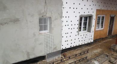 Zateplení fasády polystyrenem. Na fasádě je již natažené lepidlo s perlinkou