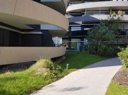 Chodník mezi bytovými domy postavený z drenážního betonu