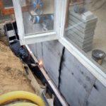 Hydroizolace základů domu asfaltovými pásy.